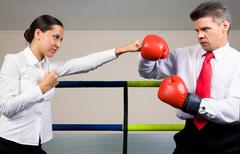 Stock Photo of portrait of aggressive businessman in boxing gloves fighting with serious female