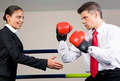 Portrait of aggressive businessman in boxing gloves fighting with positive femal Stock Photos
