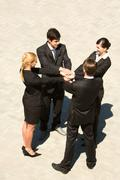 photo of people standing and stacking their hands - stock photo