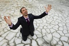 Photo of helpless businessman standing on dry ground and raising his arms upward Stock Photos