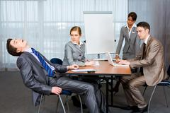 Photo of displeased businesspeople looking sternly at snoring man at presentatio Stock Photos