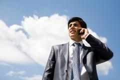 portrait of confident businessman calling by cellular phone against cloudy sky - stock photo