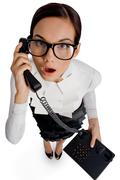above view of amazed woman in eyeglasses speaking on the phone and looking at ca - stock photo