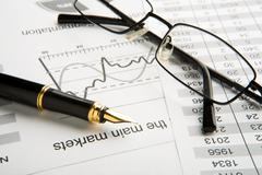 Close-up of fountain pen, eyeglasses and financial documents Stock Photos