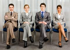 Portrait of confident business group sitting in row and looking at camera Stock Photos