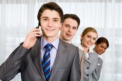 photo of happy leader calling his partner with smiling employees looking out of - stock photo