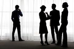 four outlines of business partners communicating with calling male near by - stock photo