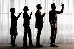 silhouettes of contemporary business people standing in line with pointing foref - stock photo