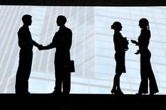 outlines of business partners handshaking with two communicating females near by - stock photo