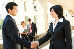 photo of successful people handshaking with working partners at background - stock photo