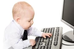 Stock Photo of photo of cute baby typing on keyboard with monitor in front of him