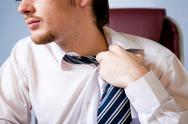 Stock Photo of close-up of annoyed businessman loosing his tie to relax a bit after hard work