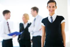 portrait of attractive business lady looking at camera with smile on background - stock photo