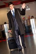 Portrait of handsome businessman walking down the airport and saying goodbye Stock Photos