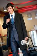 Image of happy guy in suit and coat standing with his baggage and newspaper in t Stock Photos
