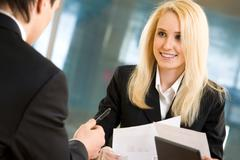 photo of blond businesswoman looking at her colleague while he explaining his id - stock photo