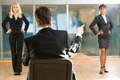 Rear view of boss pointing at one of female employees standing in front of him i Stock Photos