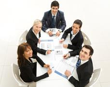 Several white collar workers sitting around table and looking upwards with smile Stock Photos