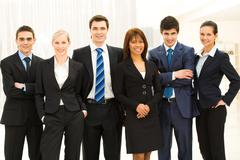 portrait of smart business people standing next to each other and looking at cam - stock photo