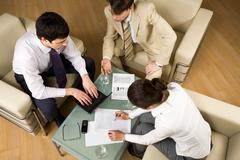 view of three business partners discussing new plan around table - stock photo