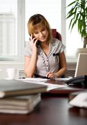 portrait of executive woman talking on the phone with client of corporation wher - stock photo