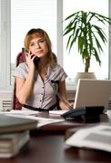 photo of helpful female speaking on the phone in office with serious expression - stock photo