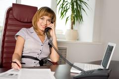 portrait of female manager speaking on the phone and looking at camera with smil - stock photo