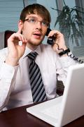 Photo of smart business leader explaining something on the phone and pointing hi Stock Photos