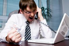 image of aggressive boss yelling into telephone receiver to one of his employees - stock photo