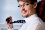 Stock Photo of smart ceo looking at camera with smile and holding his rolled tie