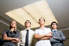 portrait of smart associates standing in row and looking upwards seriously - stock photo