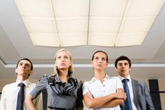 Several confident employees standing in row and looking upwards seriously Stock Photos