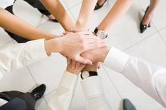 above view of business partners hands on top of each other symbolizing teamwork - stock photo