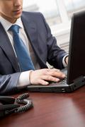 close-up of businessman's hand pressing keys of laptop in office - stock photo