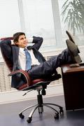 Portrait of handsome employee having rest in arm-chair in office Stock Photos