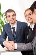 photo of successful business partners handshaking after striking deal with their - stock photo