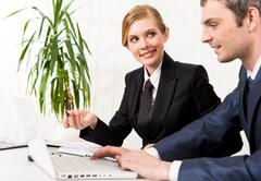 portrait of executive employee looking at business partner while explaining her - stock photo