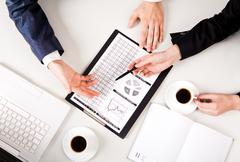 above view of business people hands while discussing documents at meeting - stock photo