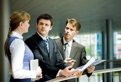 Two confident businessmen looking at pretty specialist sharing her ideas Stock Photos