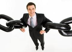 portrait of powerful businessman holding two sections of huge chain by arms over - stock photo