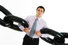 Portrait of helpless businessman holding two sections of huge chain and looking Stock Photos