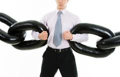Powerful businessman holding sections of huge chain over white background Stock Photos