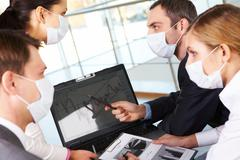 Serious business partners in protective mask looking at screen of laptop in work Stock Photos