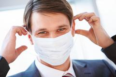 Portrait of businessman with protective mask going to put it on Stock Photos
