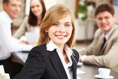 portrait of successful business lady looking at camera on background of her coll - stock photo