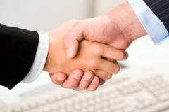 photo of handshake of business partners after signing promising contract - stock photo