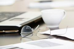 Close-up of papers, glasses and cup on workplace Stock Photos