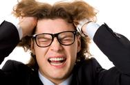 Stock Photo of close-up of smart man in eyeglasses screaming while touching his head