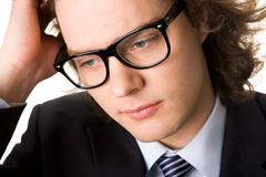 portrait of pensive businessman wearing eyeglasses - stock photo