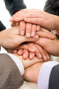 Image of business people hands on top of each other symbolizing support and powe Stock Photos